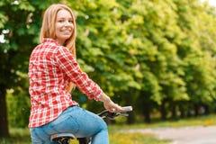 Blonde Dame mit ihrem Fahrrad Stockbild