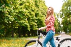 Blonde Dame mit ihrem Fahrrad Stockfotografie