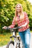 Blonde Dame mit ihrem Fahrrad Lizenzfreie Stockfotografie