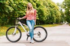 Blonde Dame mit ihrem Fahrrad Lizenzfreies Stockfoto
