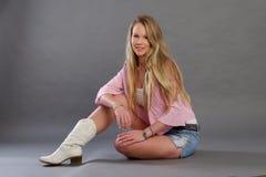 Blonde Dame mit kurzen Hosen und weißen Stiefeln Lizenzfreies Stockbild
