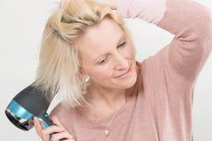 Blonde Dame Smiling While Drying ihr Haar unter Verwendung des Schlag-Trockners Stockbilder