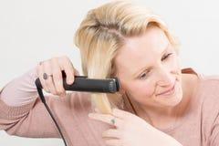 Blonde Dame Straightening Her Hair met een Ijzer royalty-vrije stock foto's