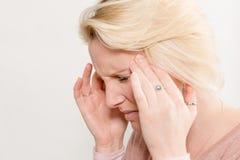 Blonde Dame Touching Sides van Hoofd in de Ruimte van het Pijnexemplaar stock afbeelding