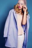 Blonde Dame trägt eleganten Mantel, Bluse, Hosen und luxuriöse Halskette Lizenzfreie Stockfotos