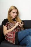 Blonde Dame Yong mit einem Mobiltelefon Stockfotos