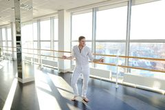 Blonde male person spotting in white suit. Blonde dancer raving in and doing spot. Young man wears white suit. Concept of rotating body and head Stock Photos
