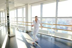 Blonde male person spotting in white suit. Blonde dancer raving in and doing spot. Young man wears white suit. Concept of rotating body and head Royalty Free Stock Photography