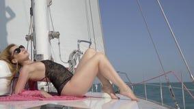 Blonde dans des lunettes de soleil prenant un bain de soleil sur un yacht flottant sur la mer, tir au ralenti Luxe, maquillage clips vidéos