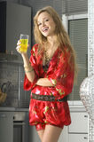 Blonde dans la cuisine moderne avec du jus Photo stock