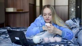 Blonde dans le lit se reposant, travaillant dans un ordinateur portable, mangeant le dessert en journée banque de vidéos