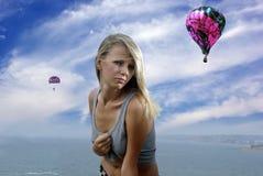 Blonde dans une chemise contre le ciel et la mer Image stock