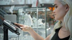 Blonde de femme, achats de mannequin payant avec la technologie de NFC au téléphone portable, dans le supermarché banque de vidéos