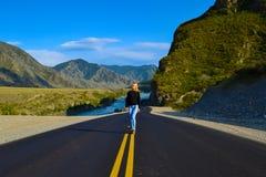 Blonde de fille sur une route goudronnée noire avec les taches et le San jaunes photo libre de droits