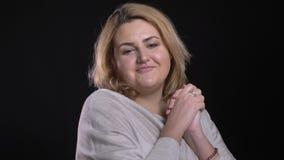 Blonde de kortharige te zware beambte op middelbare leeftijd springt het tonen van geluk in camera op zwarte achtergrond stock videobeelden