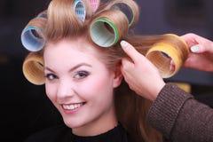 Blonde de krulspeldenrollen van het meisjeshaar door kapper in herenkapper royalty-vrije stock fotografie
