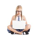 Colegiala que lleva un uniforme escolar que se sienta en el piso con un ordenador portátil en su revestimiento Foto de archivo