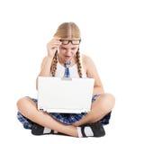 Colegiala que lleva un uniforme escolar que se sienta en el piso con un ordenador portátil en su revestimiento Imagen de archivo