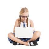 Colegiala que lleva un uniforme escolar que se sienta en el piso con un ordenador portátil en su revestimiento Fotos de archivo