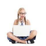 Colegiala que lleva un uniforme escolar que se sienta en el piso con un ordenador portátil en su revestimiento Imágenes de archivo libres de regalías