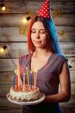 Blonde de la muchacha en un casquillo con la torta de cumpleaños en sus manos Imágenes de archivo libres de regalías