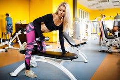 Blonde de la muchacha que hace ejercicios en el gimnasio La muchacha entra para los deportes en el gimnasio concepto de una forma Foto de archivo