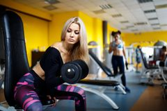 Blonde de la muchacha que hace ejercicios en el gimnasio La muchacha entra para los deportes en el gimnasio concepto de una forma Imagenes de archivo