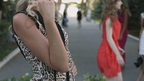 Blonde in de luipaardkleding die in openlucht stellen stock video