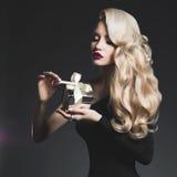 Blonde de lujo con un regalo foto de archivo