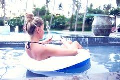 Blonde de sourire à l'aide du smartphone dans la piscine dans un jour ensoleillé travail photo stock