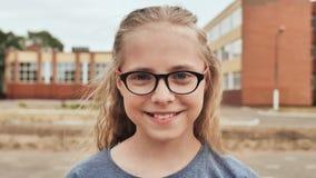 Blonde de sourire fille de 11 ans avec des verres banque de vidéos
