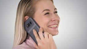 Blonde de sourire parlant au téléphone sur le fond de gradient images stock