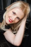 Blonde de sourire sensuelle avec les languettes rouges Photo stock