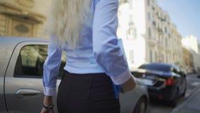 Blonde delgado hermoso que camina con confianza a lo largo del camino, buscando su coche almacen de metraje de vídeo