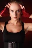 Blonde di posizione attraente nei guanti di sport di colore rosso Immagini Stock