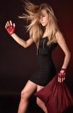 Blonde di posizione attraente nei guanti di sport di colore rosso fotografie stock libere da diritti