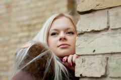 Blonde dichtbij de bakstenen muur Royalty-vrije Stock Afbeeldingen