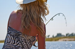 Blonde die bij rivier vist Stock Foto's