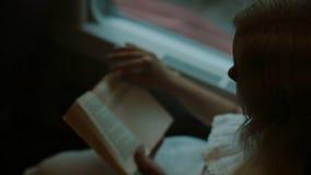 Blonde die een boek in de trein lezen stock video