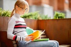 Blonde die in glazen met notitieboekjes op bank zitten Stock Foto's