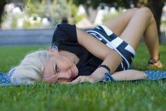 Blonde die op een gras liggen Stock Afbeeldingen
