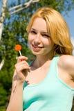 Blonde die suikergoed in het park likt stock foto