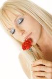 Blonde die van bloem geniet Royalty-vrije Stock Afbeeldingen