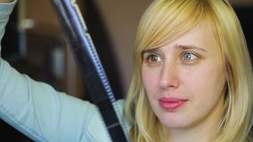 Blonde with different eyes examines retro film, heterochromia. HD footage stock footage