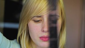 Blonde with different eyes examines retro film, heterochromia stock video