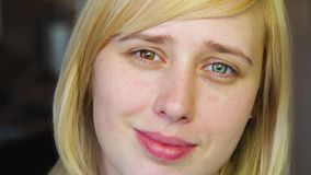 Blonde with different eyes looks at the camera and smiles, heterochromia stock footage