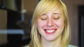 Blonde with different eyes looks at the camera and smiles, heterochromia, In slow motion stock video footage