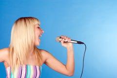 Blonde divertido en un azul con un micrófono Imagen de archivo