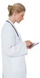 Blonde doctor in lab coat using tablet pc Stock Photo