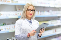Blonde doctor in white uniform using tablet and technology in pharmaceutical or medical field Royalty Free Stock Photography